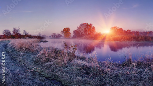 Aluminium Herfst Sunrise on autumn frosty nature. Landscape of bright dawn over river. grass with hoarfrost shining on sun lights