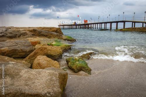 Fotobehang Bleke violet Cold morning seascape with rocky beach and pier, Konakli Turkey.