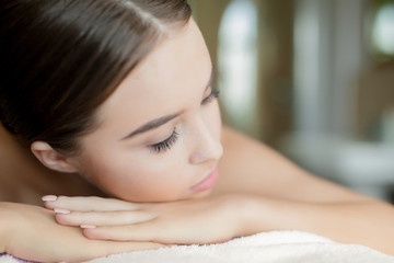 Girl with closed eyes enjoying rest and bodycare treatment in dayspa salon