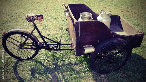 Fotobehang Fiets ancient wooden cart with old bicycle to transport the milk j