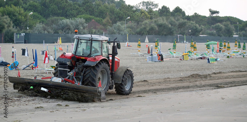 Fotobehang Trekker tractor that cleans the beach at dawn from the waste of the day