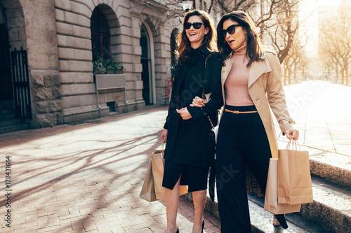 Obraz na płótnie Happy female shoppers carrying shopping bags