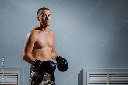 handsome man or healthy boxer or Thai boxer with six pack wearing boxing gloves Poster