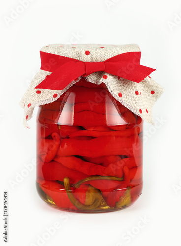 Foto op Canvas Hot chili peppers Jar of pickled red hot chili peppers over white