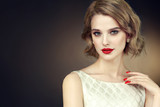 Beautiful model girl with short curly  hair and red lips . Red manicure on nails .Beauty and esthetic care  - 178470822