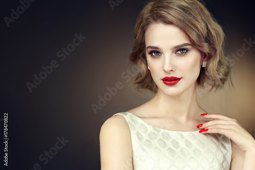 Foto op Canvas Kapsalon Beautiful model girl with short curly hair and red lips . Red manicure on nails .Beauty and esthetic care