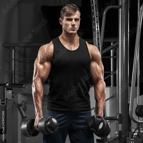 Poster Muscular man working out in gym doing exercises, strong male torso