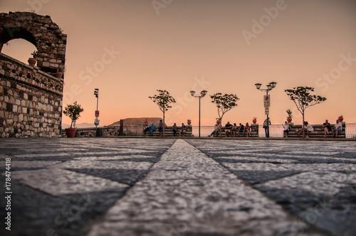 Papiers peints Saumon PIazza con pavimento chiaro scuro al tramonto con visitatori che si riposano su panchine