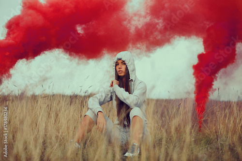 Portrait of a young woman in a meadow with smoke bomb in the background Poster