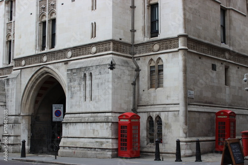Red telephone boxes in front of a building Poster