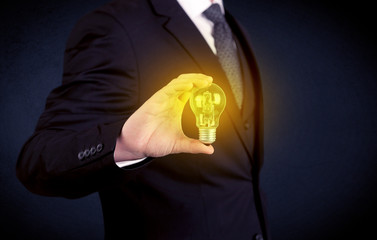 man in suit holding a glowing yellow light bulb