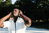 Black man listening to music in a city park - 178536452