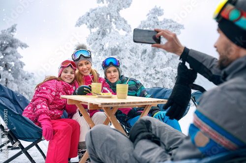 Family takes tea break during skiing on the mountain
