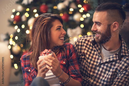 Female looking at male while holding Christmas present