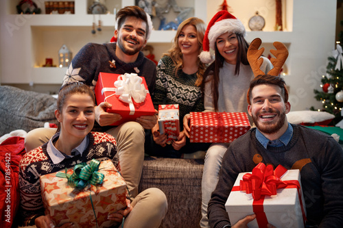 Cheerful friends holding boxes with Christmas gifts