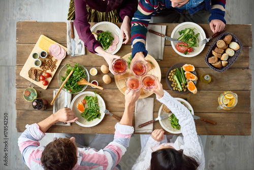Top view of four people eating at festive dinner table with delicious food in cafe or restaurant clinking glasses