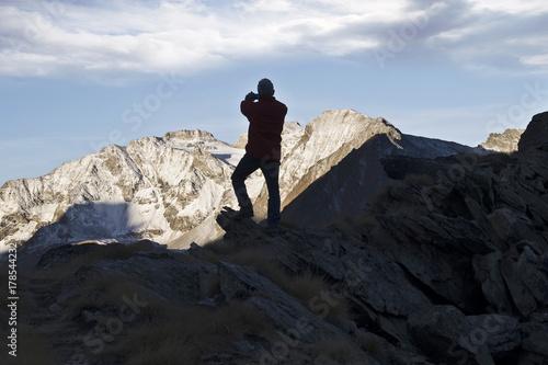 Papiers peints Noir L'escursionista fotografa la montagna illuminata dal sole.