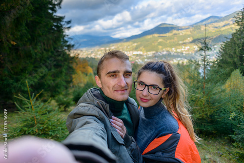 Happy lucky couple makes a self portrait against the background of mountains and towns Poster