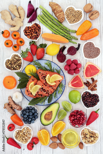 Health food for a healthy heart with salmon, vegetables, fruit, nuts, seeds, spices and herbs used in herbal medicine. Super food concept, high in omega 3, anthocyanins, antioxidants and vitamins. © marilyn barbone