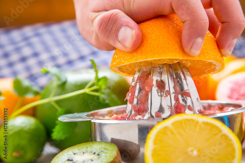 Foto op Plexiglas Sap Preparation of orange grape or multivitamin juice, hands squeeze juice on a manual metal juicer surrounded by fresh tropical fruit