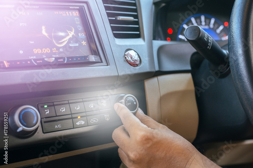 Hand of man turning on car air conditioning system,Button on dashboard in car panel