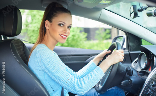 pretty smiling girl driving a car
