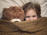 Child and toy bear under blanket in bed - 178567892
