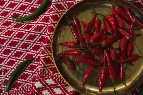 Red chilies in plate on table cloth Poster