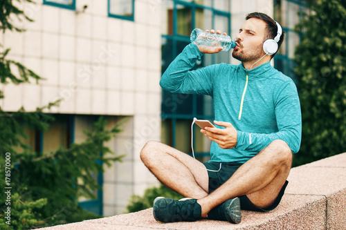 Fotobehang Muziek Man is relaxing after jogging