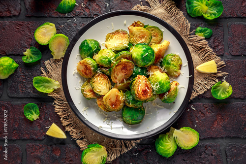 Foto op Canvas Brussel Homemade Roasted Brussel Sprouts with Parmesan cheese, lemon, Salt, Pepper on a old stone rustic table.