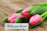Welcome home card with three pink tulips on wooden surface - 178573262