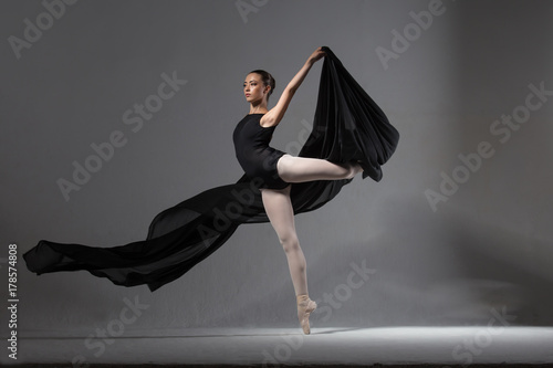 Plakat Graceful ballerina in black tights posing with black cloth
