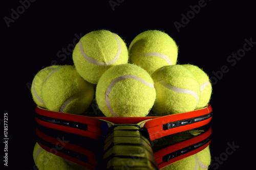 Aluminium Tennis Tennis racket and pile of tennis balls on black reflective surface.