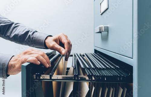 Office clerk searching for files © stokkete