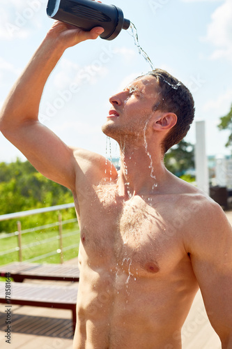 Waist up portrait of muscular young man with bare torso pouring water refreshing after working out outdoors in sunlight