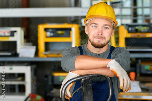 Foto Murales Portrait of cheerful young worker wearing hardhat posing looking at camera and smiling enjoying work at modern factory