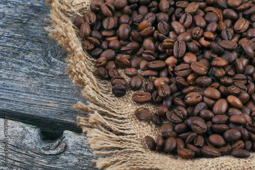 Papiers peints Café en grains Fried coffee beans on jute and on old boards
