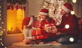 Merry Christmas! happy family mother father and child with magic gift near tree. - 178598840
