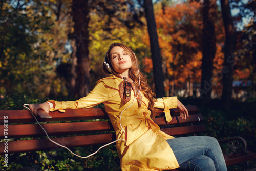 Fotobehang Muziek Young woman enjoys music through the headphones in the park