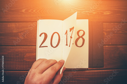 New Year 2018 is coming concept. Hand flips notepad sheet on wooden table. 2017 is turning, 2018 is opening