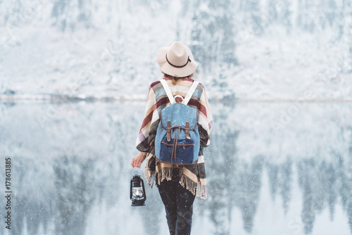 Traveling woman standing in the wild in front of amazing lake view with oil lamp. Wearing hat, poncho and backpack. Winter is coming, first snowfall. Wanderlust and boho style