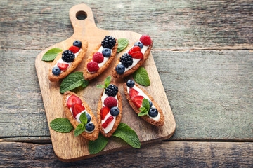 Tartlets with berries on cutting board