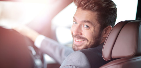 Portrait of an handsome smiling business man driving his car