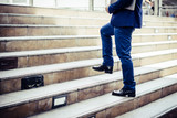 Close up of young businessman walking upstairs outside office. - 178634275