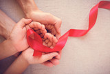 adult and child hands holding red ribbon, hiv awareness concept, world AIDS day - 178643095