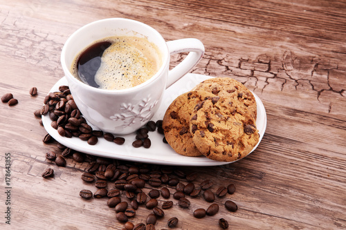 Poster Coffee cup with chocolate cookies and coffee beans on wooden background