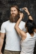 Woman combing hair of a tall bearded man