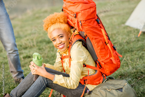 Portrait of an african woman resting with backpack and bottle outdoors on the gr Poster