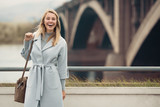 Young woman in blue coat. Autumn city background. - 178656408