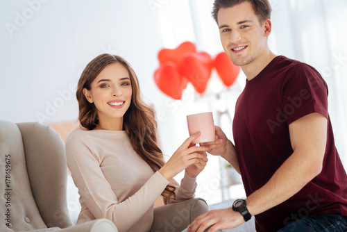 Beaming couple smiling while warming up with aromatic tea Poster